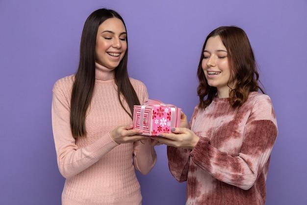 Sorridente due ragazze che tengono e guardano la confezione regalo