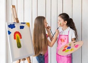 キャンバスの近くに立ってペイントブラシでお互いの顔を塗る2人の女の子の笑顔