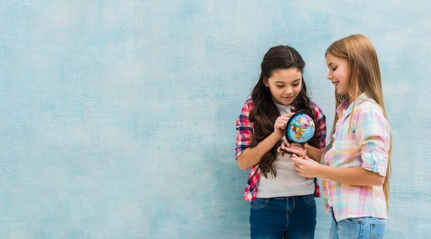 Smiling two girls standing against blue wall looking at small globe