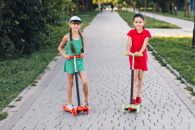 Smiling two girls standing on push scooter on walkway in the park