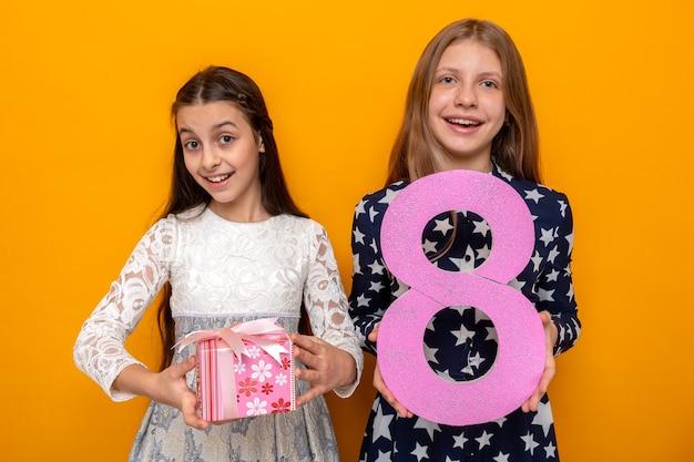 Улыбающиеся две маленькие девочки в счастливый женский день держат номер восемь с подарком