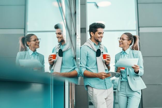 屋外に立って、仕事について話し合っている2人の多文化の同僚の笑顔。