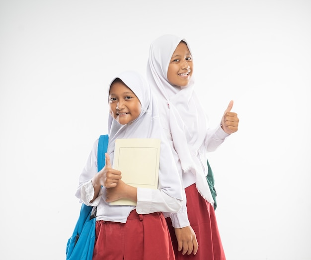 Smiling two veiled girls wearing elementary school uniforms with thumbs up carrying backpacks and a ...