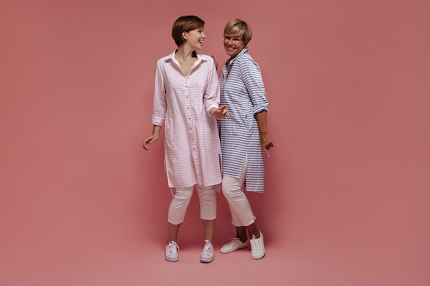 Smiling two women in good mood with short hair in striped cool shirts and white trousers dancing on isolated pink backdrop.