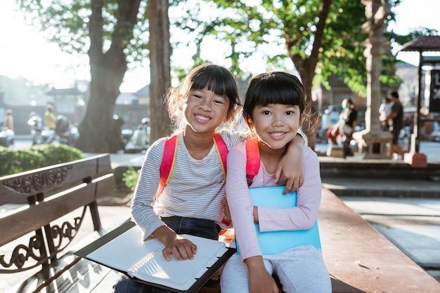 책을 들고 웃는 두 어린 소녀 학생