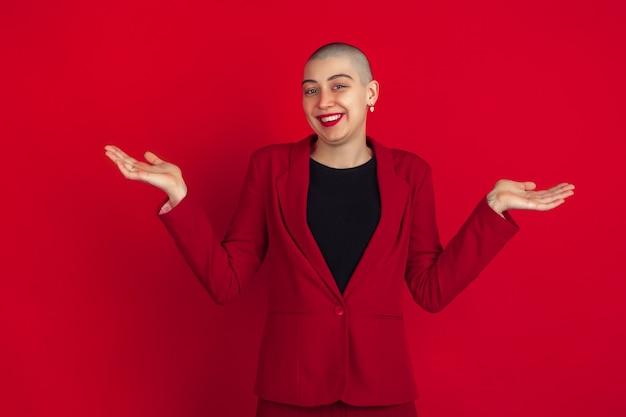 미소, 불확실. 빨간 스튜디오 벽에 격리된 젊은 백인 대머리 여성의 초상화.