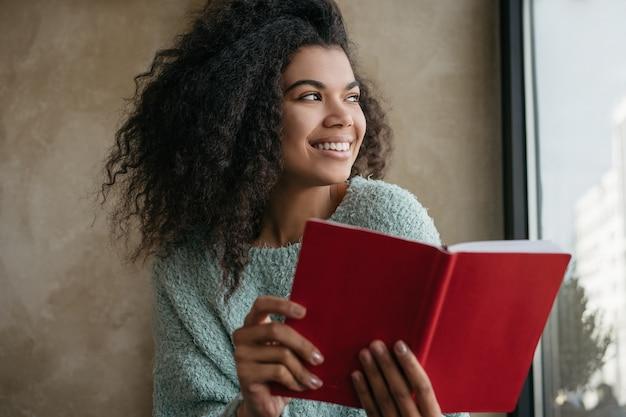 Smiling university student studying, learning language, holding red book