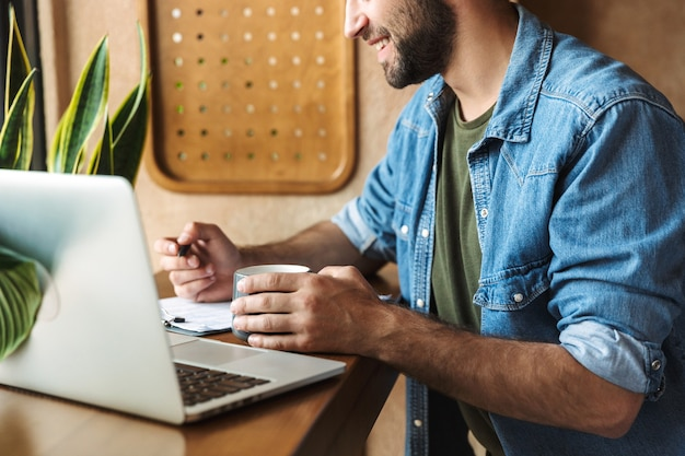 Smiling unshaven man wearing denim shirt writing and typing on laptop while working in cafe indoors