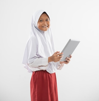 Smiling a veiled girl in elementary school uniform stands holding a digital tablet