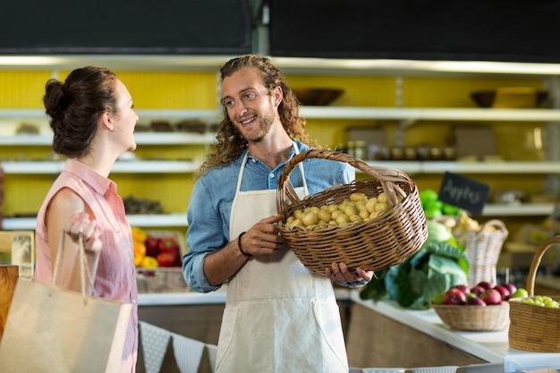 Улыбающийся продавец держит корзину с картошкой во время общения с женщиной