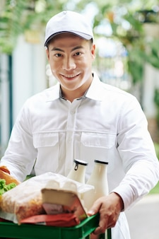 牛乳、卵、パンなどの新鮮な製品のプラスチック箱を配達する笑顔のベトナムの宅配便