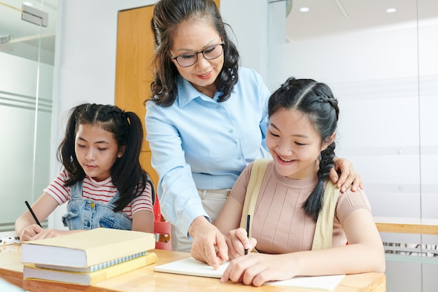 Smiling vietnamese school teacher telling student to correct mistake in copybook