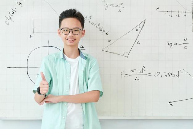 Улыбающийся вьетнамский школьник в очках стоит у доски с геометрическими формулами и рисунками и показывает палец вверх