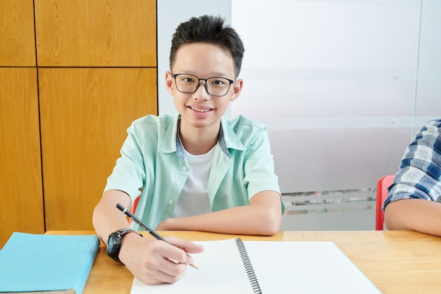 Smiling vietnamese teenage boy in glasses writing in copybook and looking