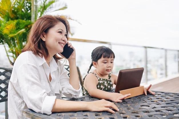 娘が近くに座ってデジタルタブレットで漫画を見ているときに電話で呼び出す笑顔のベトナム人女性