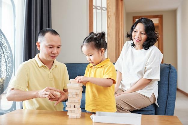Улыбающаяся вьетнамская женщина смотрит на своего мужа и маленькую дочь, строящую башню из маленьких деревянных улочек