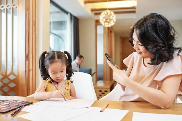 Улыбающаяся вьетнамская женщина фотографирует свою дочь, рисующую за столом