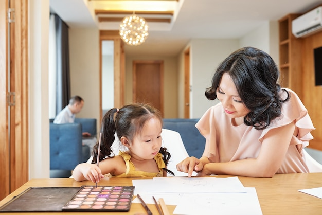Улыбающаяся вьетнамская женщина указывает на рисунок своей дочери и просит ее нарисовать больше деталей