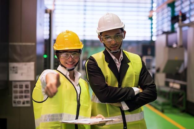 미소를 짓고 있는 여성 검사관과 남성 관리자는 공장 감사 중에 마이크로칩 반도체 기계에 엄지손가락을 치켜듭니다. 기술 산업 검사.