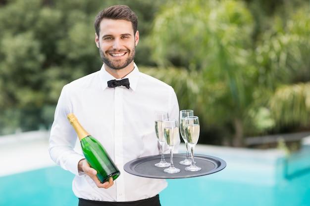 Smiling waiter holding champagne flutes and bottle