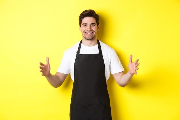 로고 또는 상자를 들고 검은 앞치마를 입은 웨이터를 웃고 노란색 배경 위에 서있는 큰 것을 들고 듯이 손을 펼칩니다.