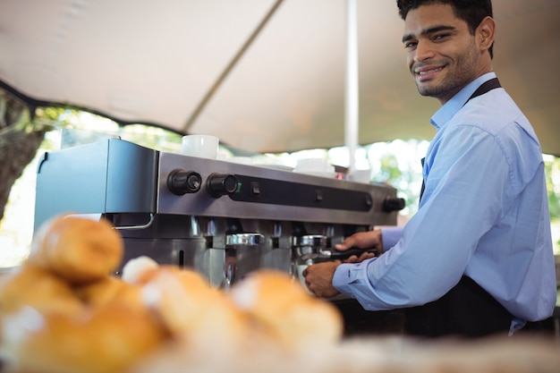 Smiling waiter making cup of coffee from espresso machine