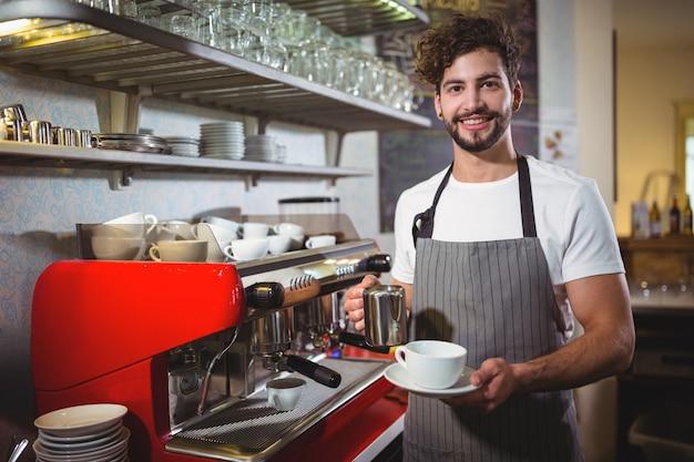 Улыбаясь официант делает чашку кофе у стойки в кафе