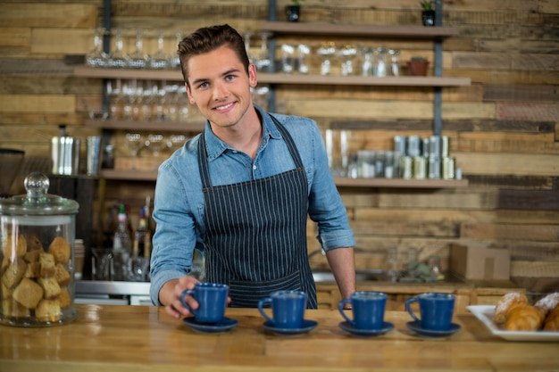 Smiling waiter preparing cup of coffee at counter