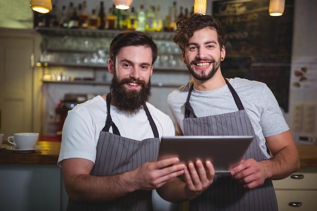 Smiling waiter using digital tablet at counter in cafã©
