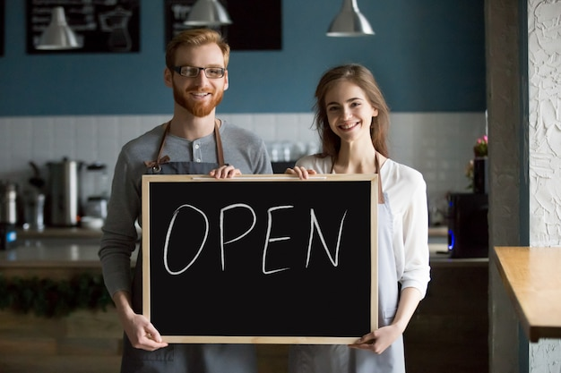 Smiling waiter and waitress holding chalkboard with open sign, portrait