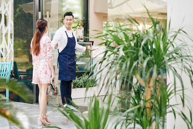 Улыбающийся официант приветствует симпатичную молодую женщину в кафе и открывает для нее дверь