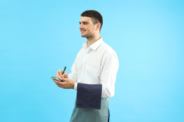 Smiling waiter with notebook on blue background.