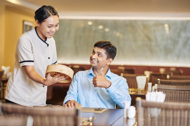 Улыбающаяся официантка подает сервировочную тарелку с восхитительными баоцзы, китайскими мясными булочками, приготовленными на пару, клиенту, сидящему за столом и показывающему большие пальцы руки