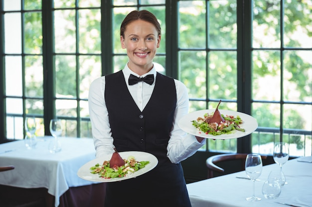 Smiling waitress holding plates