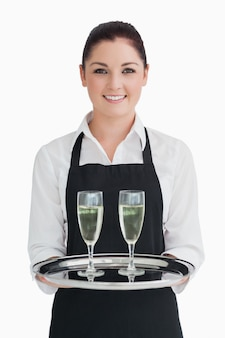 Smiling waitress holding tray with champagne