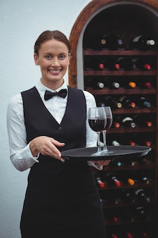 Smiling waitress holding a tray with glasses of red wine