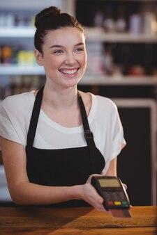 Smiling waitress showing credit card machine