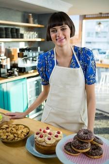 Улыбающаяся официантка стоит перед прилавком десертов и закусок