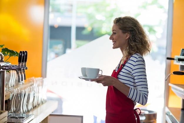 Улыбающаяся официантка стоит с чашкой кофе