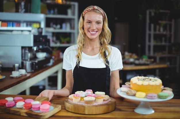 デザートと立っている笑顔のウェイトレス