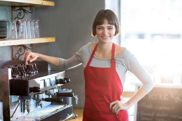 Smiling waitress standing with hand on hip at cafe