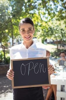 Улыбающаяся официантка, стоящая с открытой вывеской