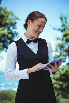 Smiling waitress taking an order with a tablet