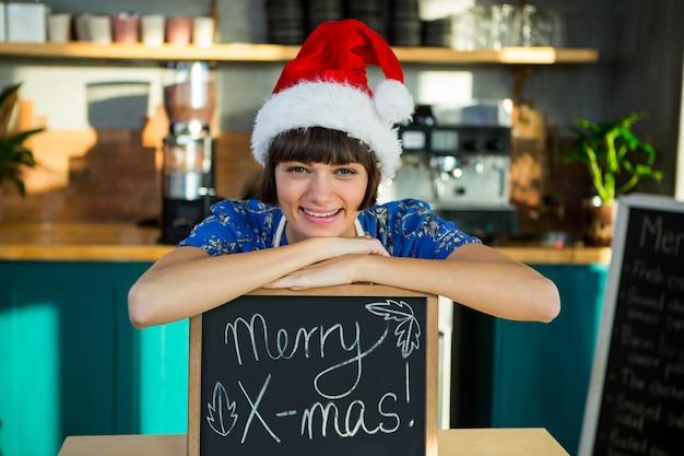 Улыбчивая официантка в новогодней шапке сидит на рождественской доске