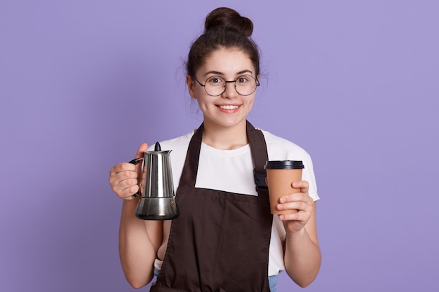 Smiling waitress in white t shirt and brown apron holding pot and take away cup in hands