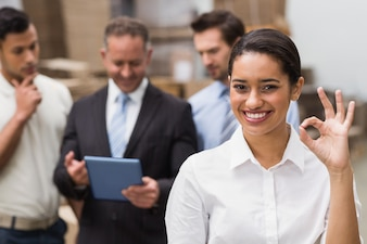 Smiling warehouse manager making okay gesture