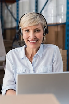 Smiling warehouse manager using laptop