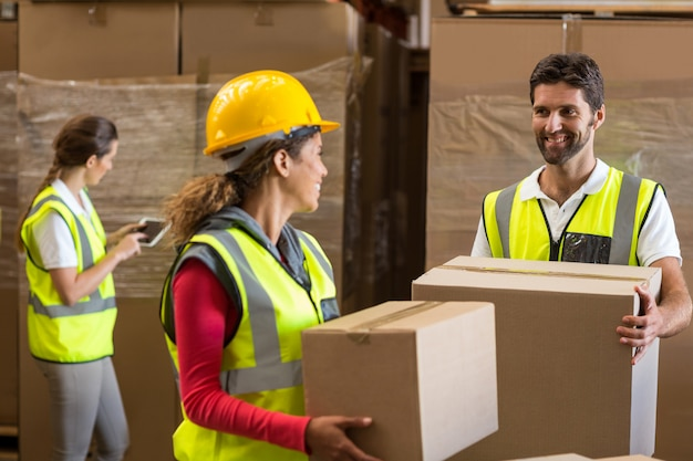 Smiling warehouse workers carrying a cardboard box