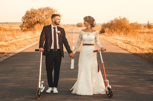 日没時に街の外の道路に沿ってスクーターに乗って笑顔の結婚式のカップル。
