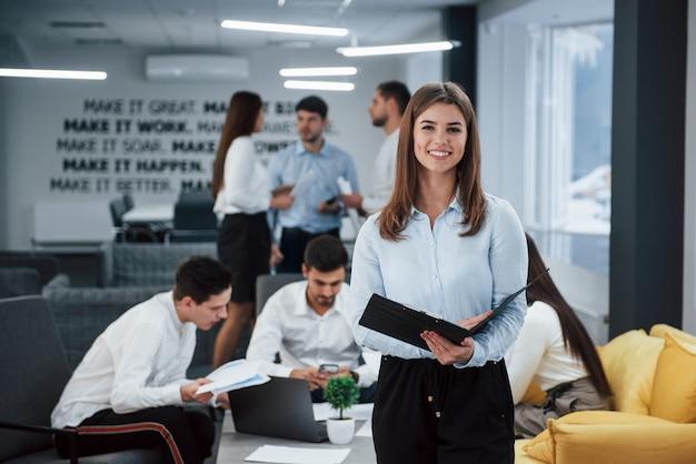 メモ帳を押しながら笑顔。バックグラウンドで従業員とオフィスに立っている若い女の子の肖像画